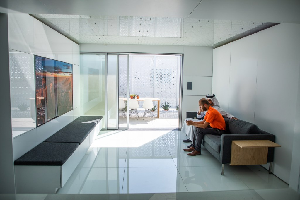 A photo of a white, futuristic home. Inside, two men sit on a couch and chat.