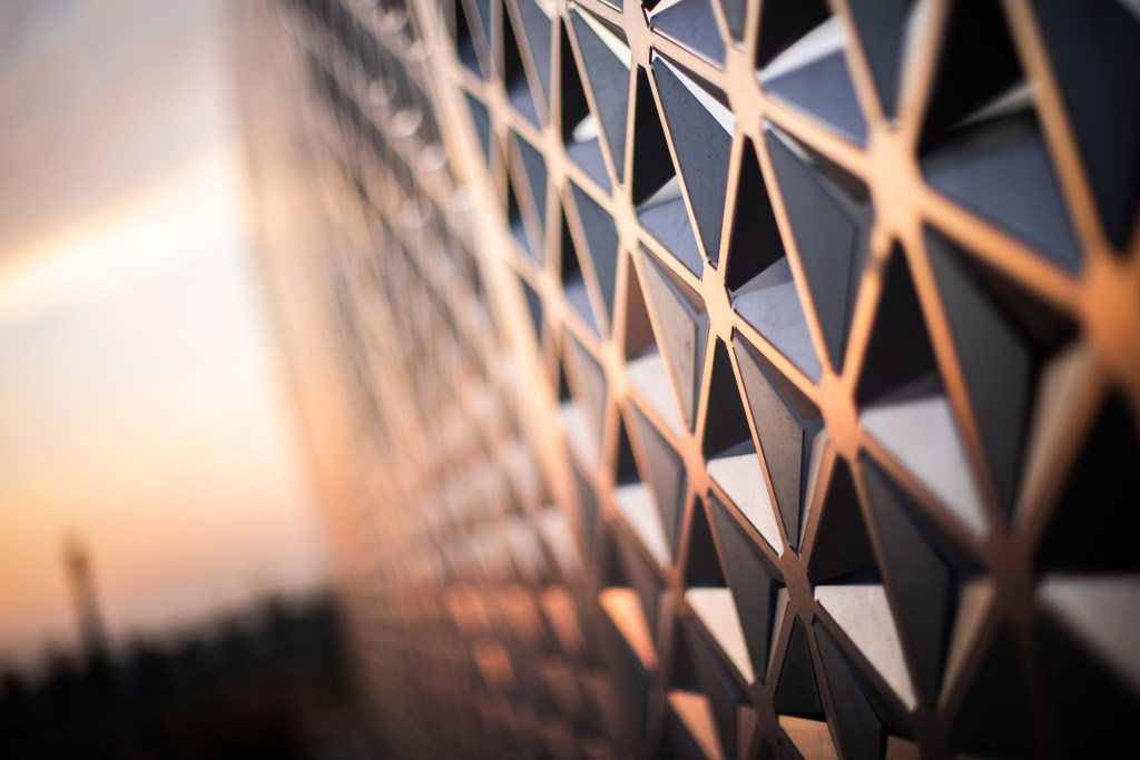 A photo of a geometric screen wall at sunset.