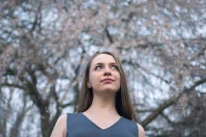 A photo of a young woman with blue eyes looking off in the distance, with a backdrop of cherry blossoms.