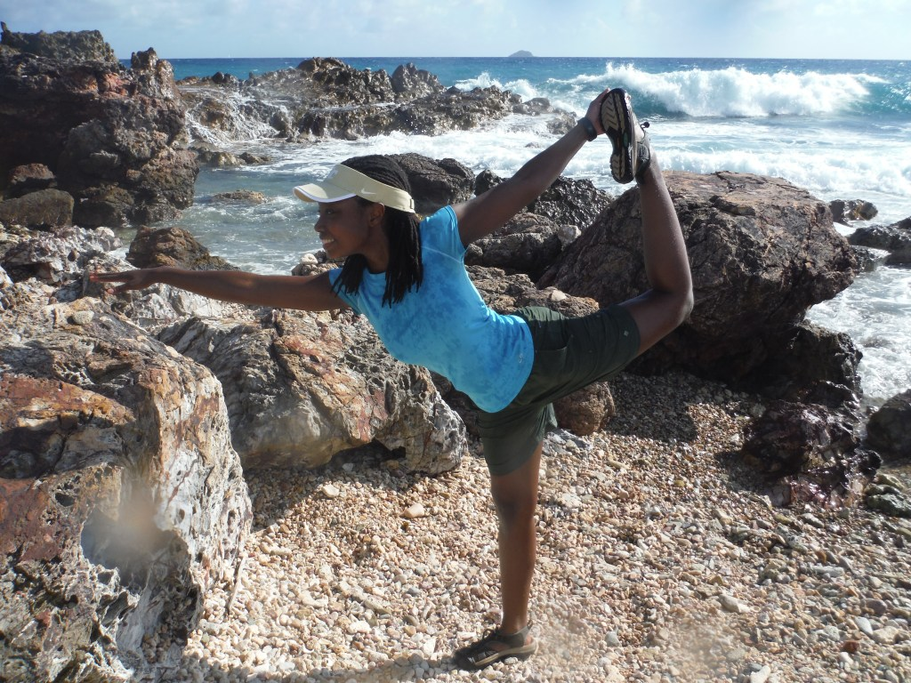 black woman with dreadlocks doing yoga poses at the beach
