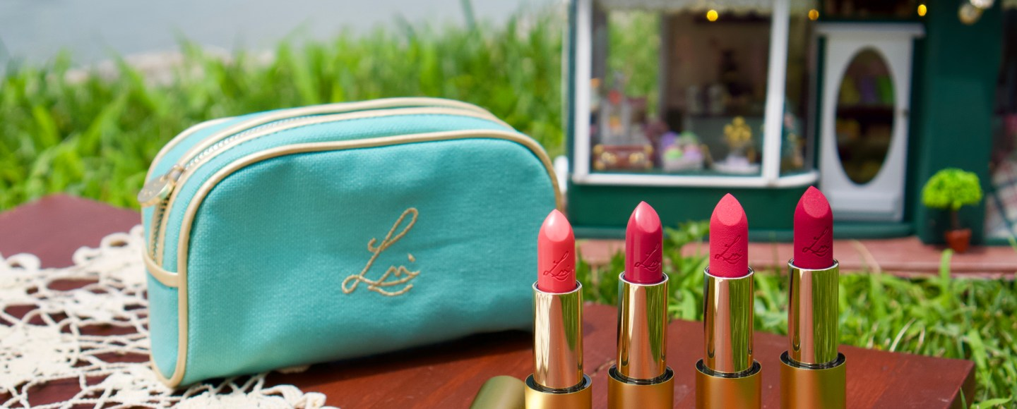 Lisa Eldridge Summer Pinks Collection Lipstick and Cosmetic Bag Display with Miniature House and Lake in Background