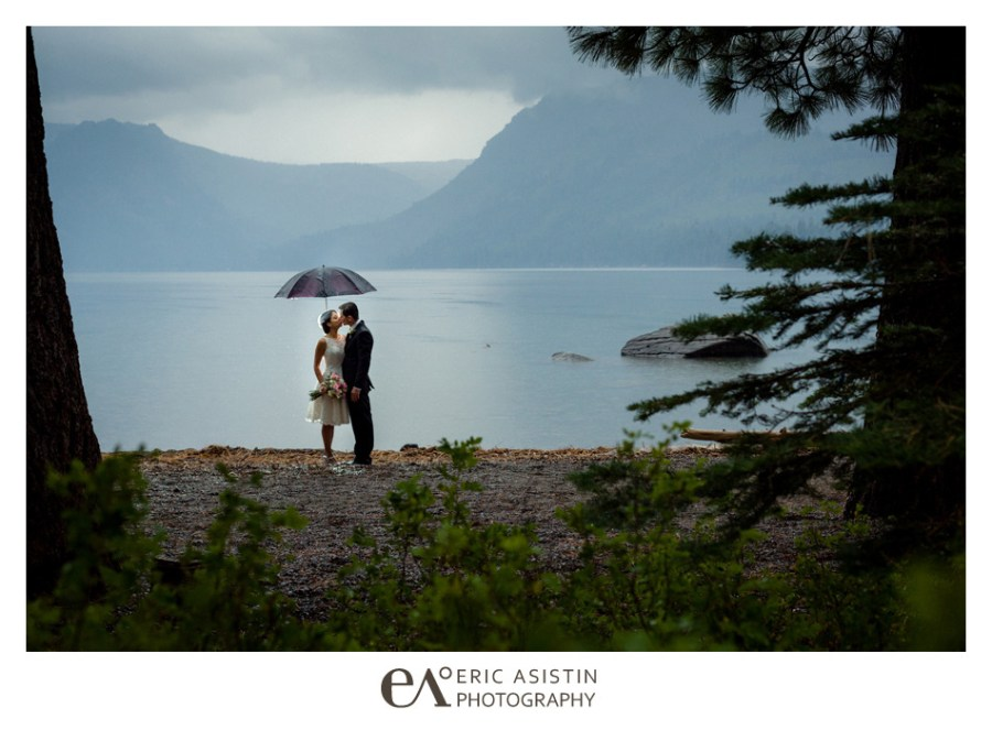 Bride and Groom kiss underneath an umbrella during their rainy day wedding elopement at Fallen Leaf Lake South Lake Tahoe.