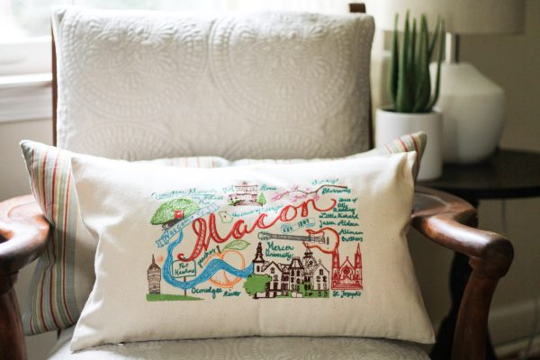 Macon Landmarks design colorfully embroidered on a pillow, sitting on a white armchair, Macon heritage gift or souvenir idea