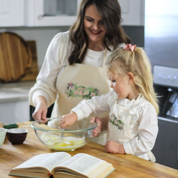 image of mother and toddler smiling while baking and wearing matching Macon Floral aprons