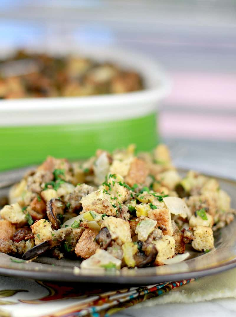 Finished presentation. Best Stuffing Recipe Ever is plated on a brown ceramic plate; the rest of the stuffing casserole is in the background in a green bake dish with white strip