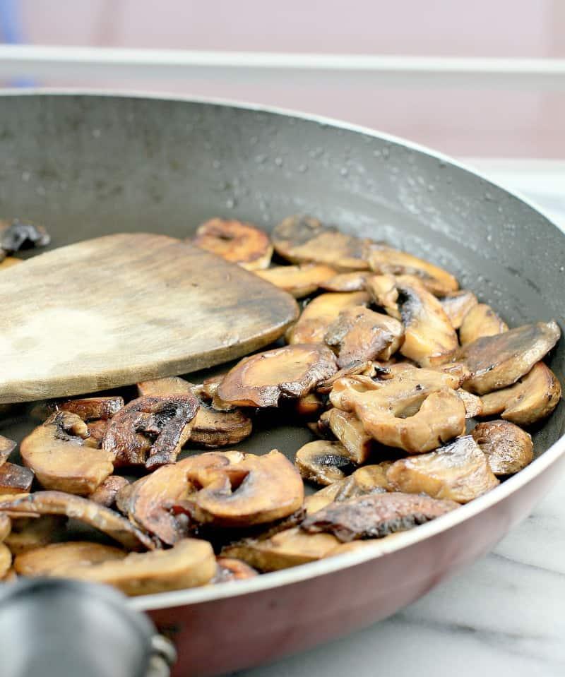 Side view of mushrooms browned in a skillet.