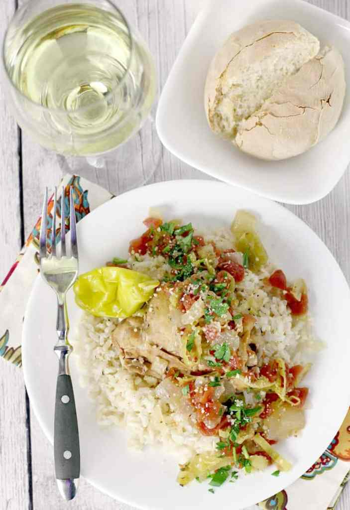 Top down view showing cooked slow cooker italian pepperoncini chicken served over rice on a white dish with a fork on the side. Bread and glass of white wine are at the top.