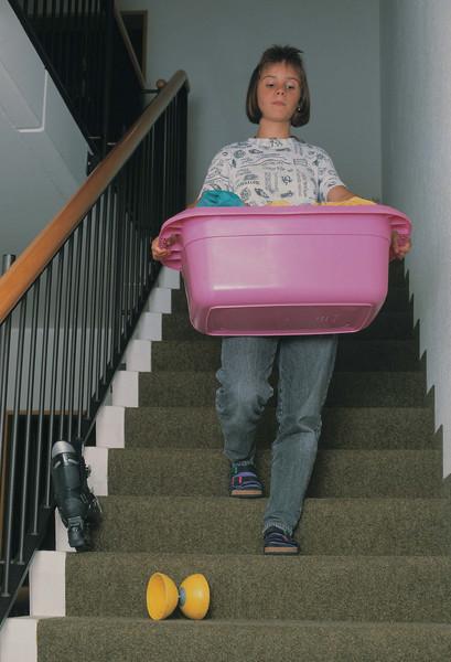 Unfallgefahr: Diabolo liegt auf der Treppe herum, Frau mit Wäschekorb kommt die Treppe herunter und sieht es nicht