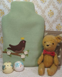 green hot water bottle cosie with brown bird applique