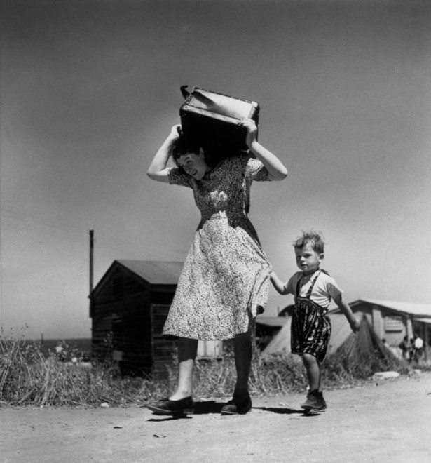 Robert Capa / Magnum Photos. ISRAEL. Haifa. 1949-50. Woman carrying luggage accompanied by a small boy.