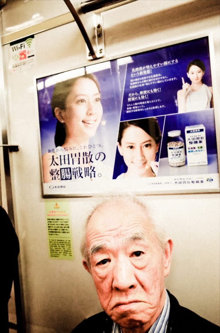 Subway street picture of man and advertisement. Tokyo, 2017