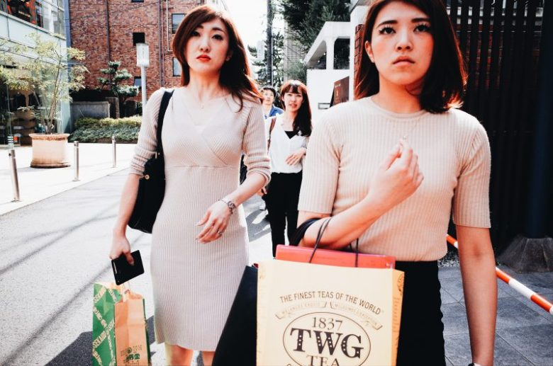 Girls with shopping bags walking towards me. I use the 'cutoff technique' to get in front of them, and to shoot head-on, to make a more dynamic street photography composition. Tokyo, 2017