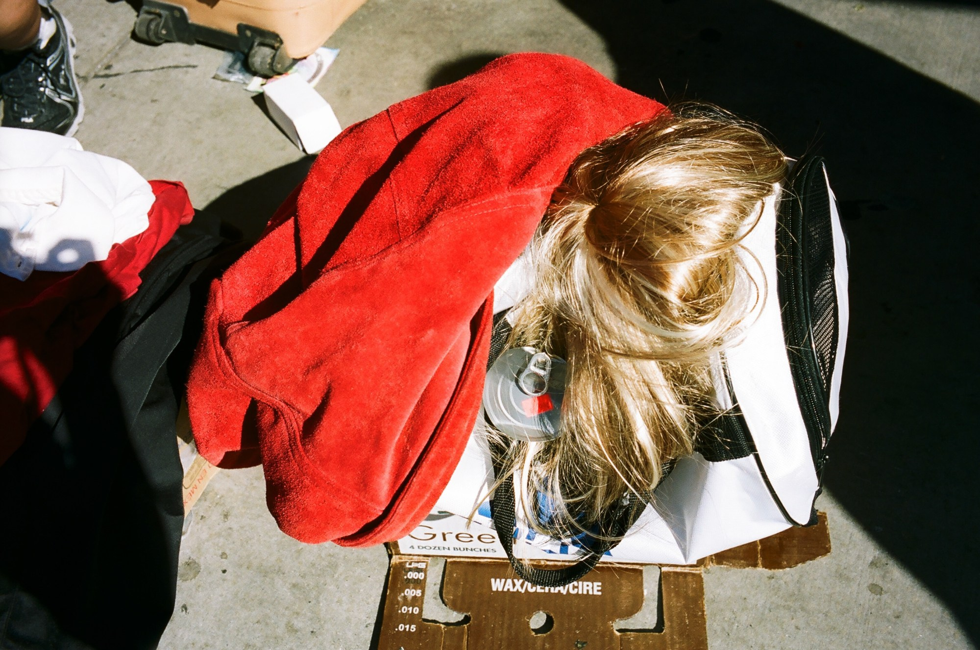 Surreal street photo by ERIC KIM: What is going on? Is there a head inside the bag? Wig and red bag