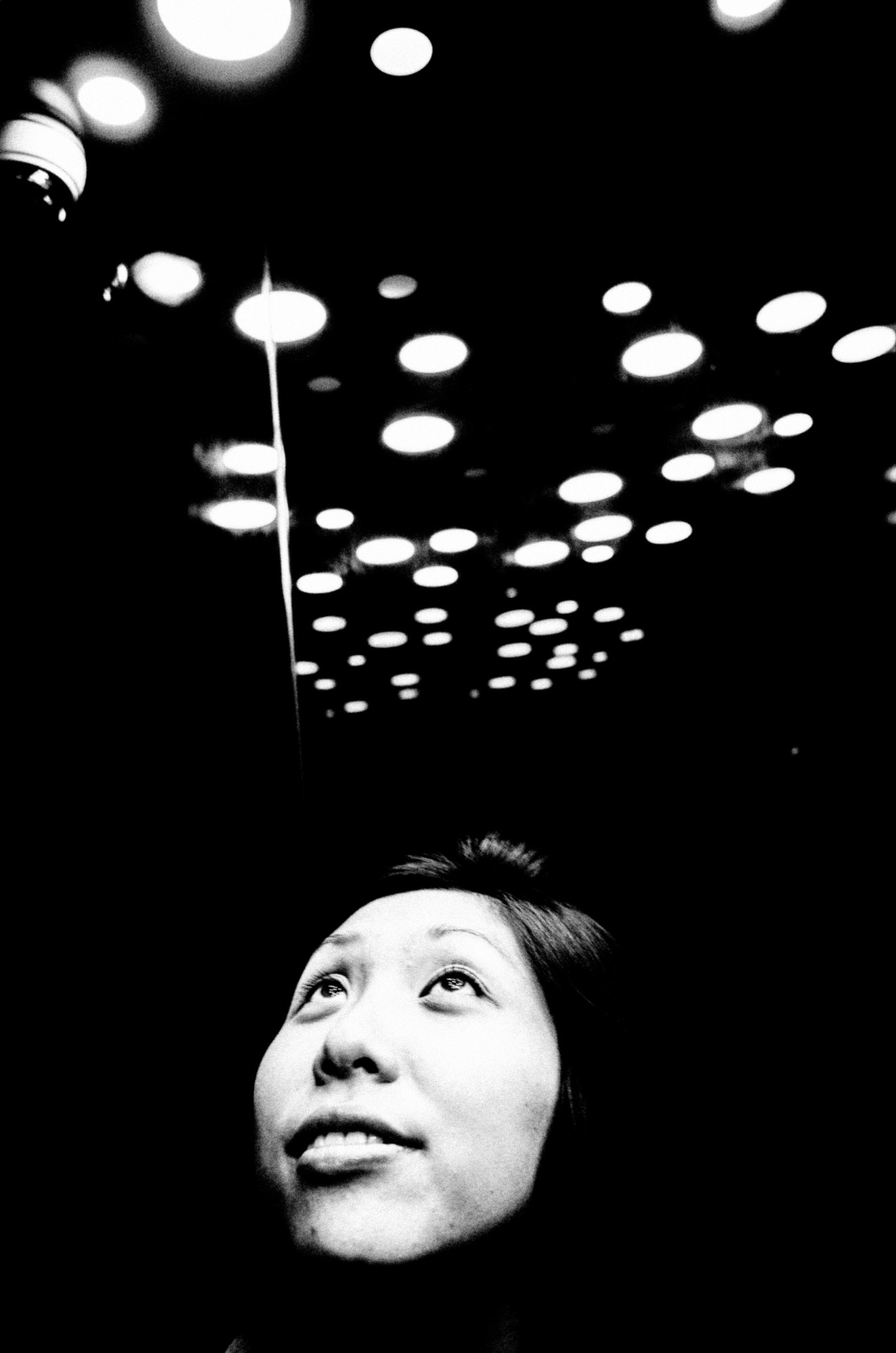 Cindy looking up in the elevator with circles. Hanoi, 2017