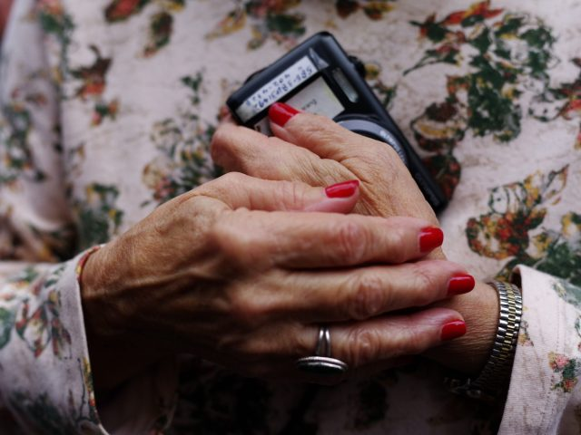 Red nails woman holding phone.