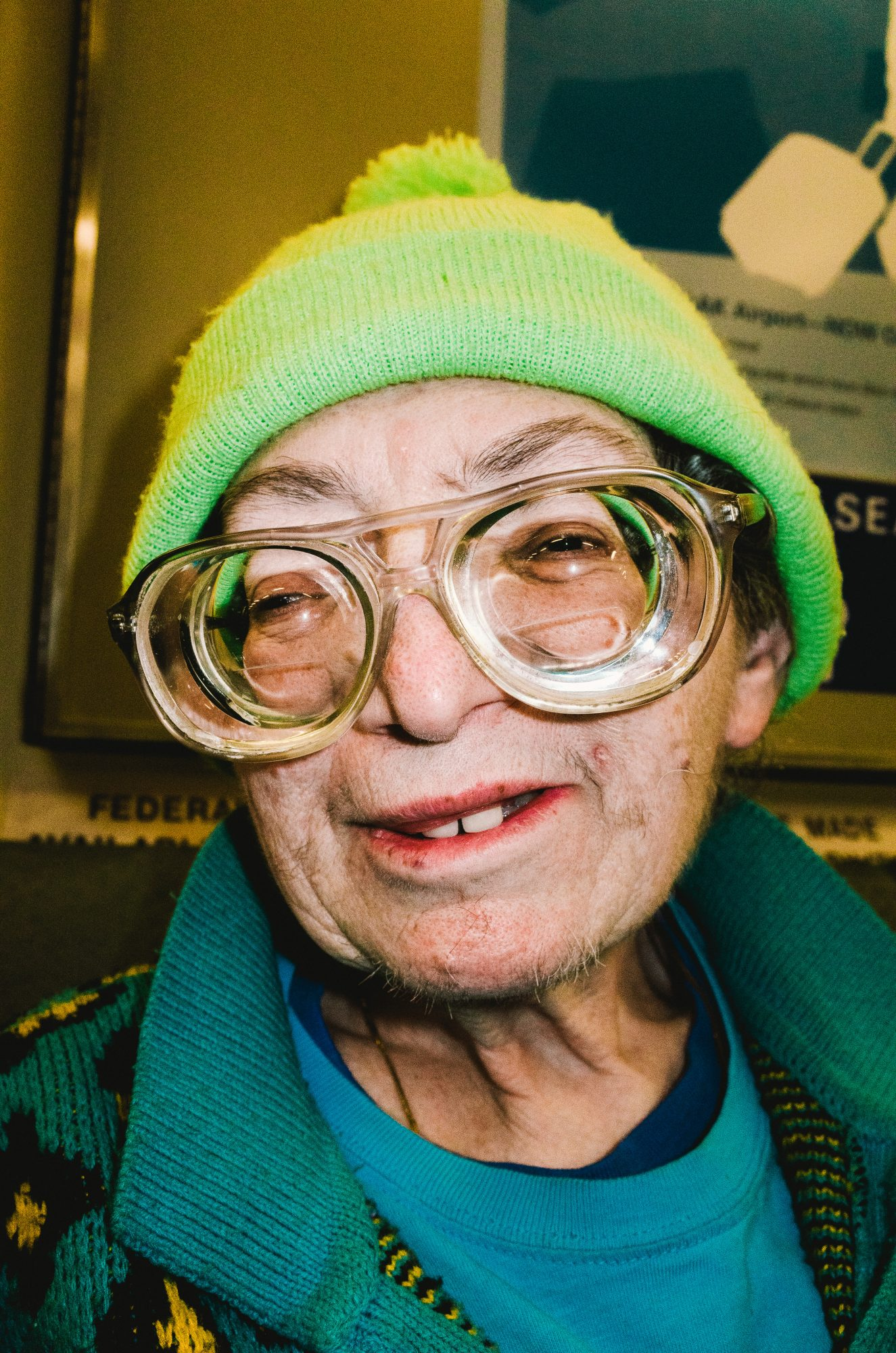 Woman with thick glasses and green hat. BART, 2015