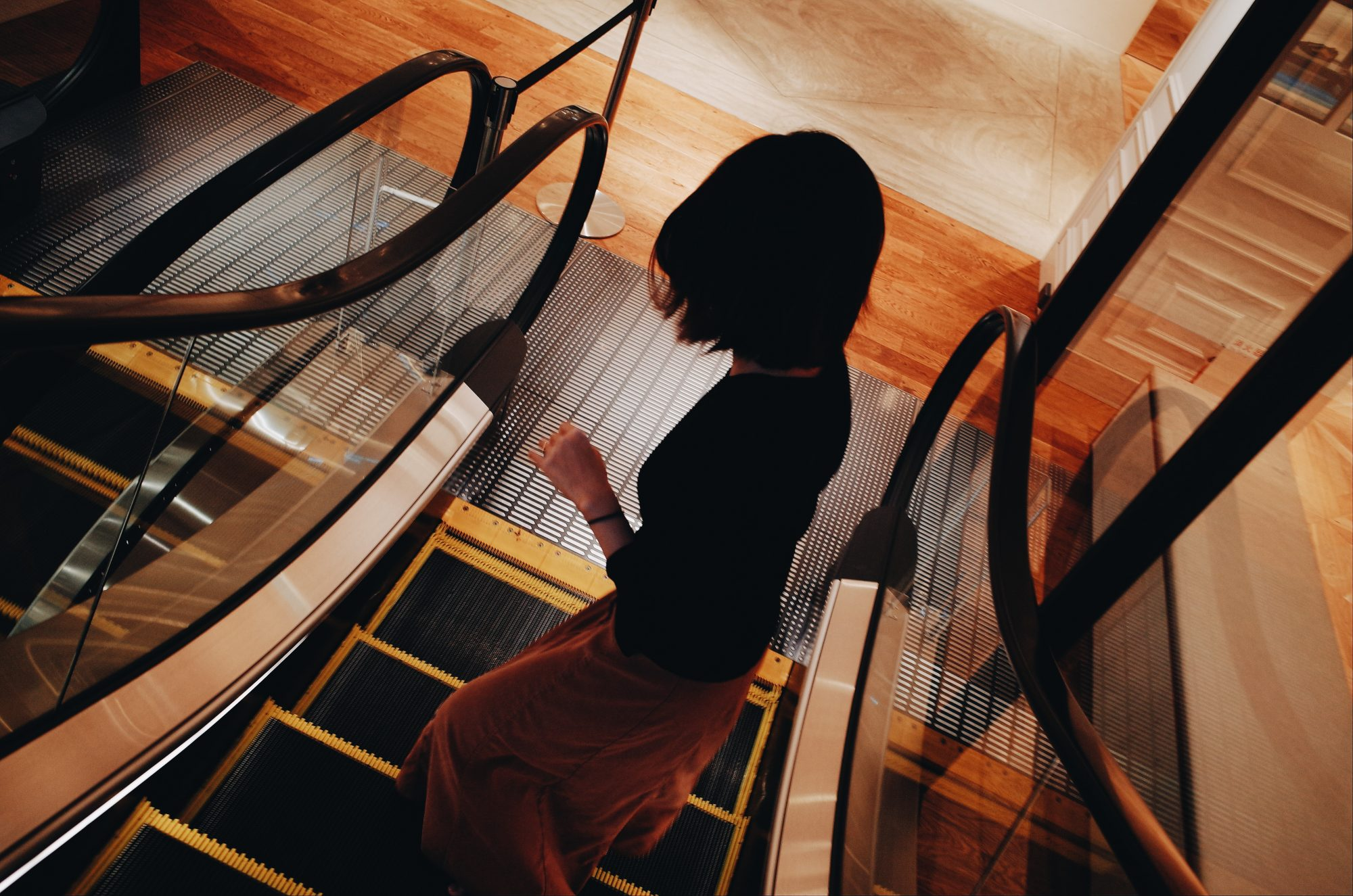 Cindy going down escalator. Shot from higher perspective, looking down. Mall, Kyoto 2017