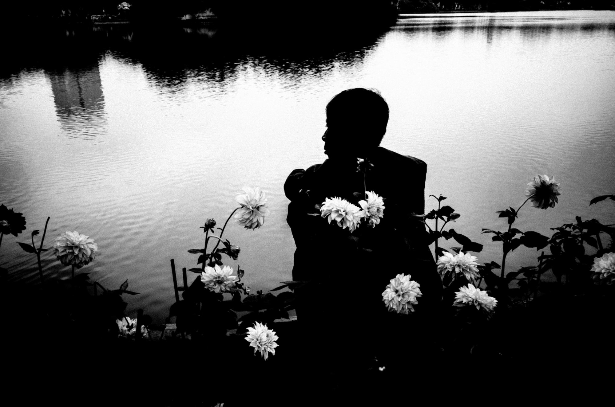 Man in silhouette. Street photograph at Hoan Kiem lake in Hanoi, 2017 / ERIC KIM