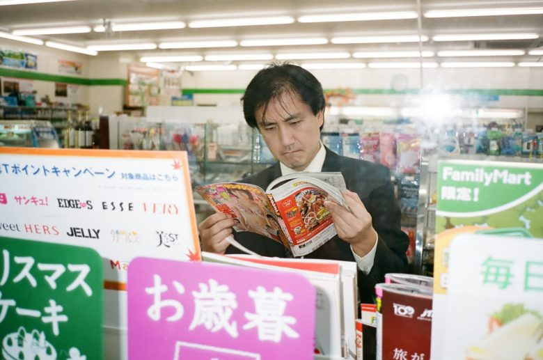 Suit looking at magazine, Kyoto