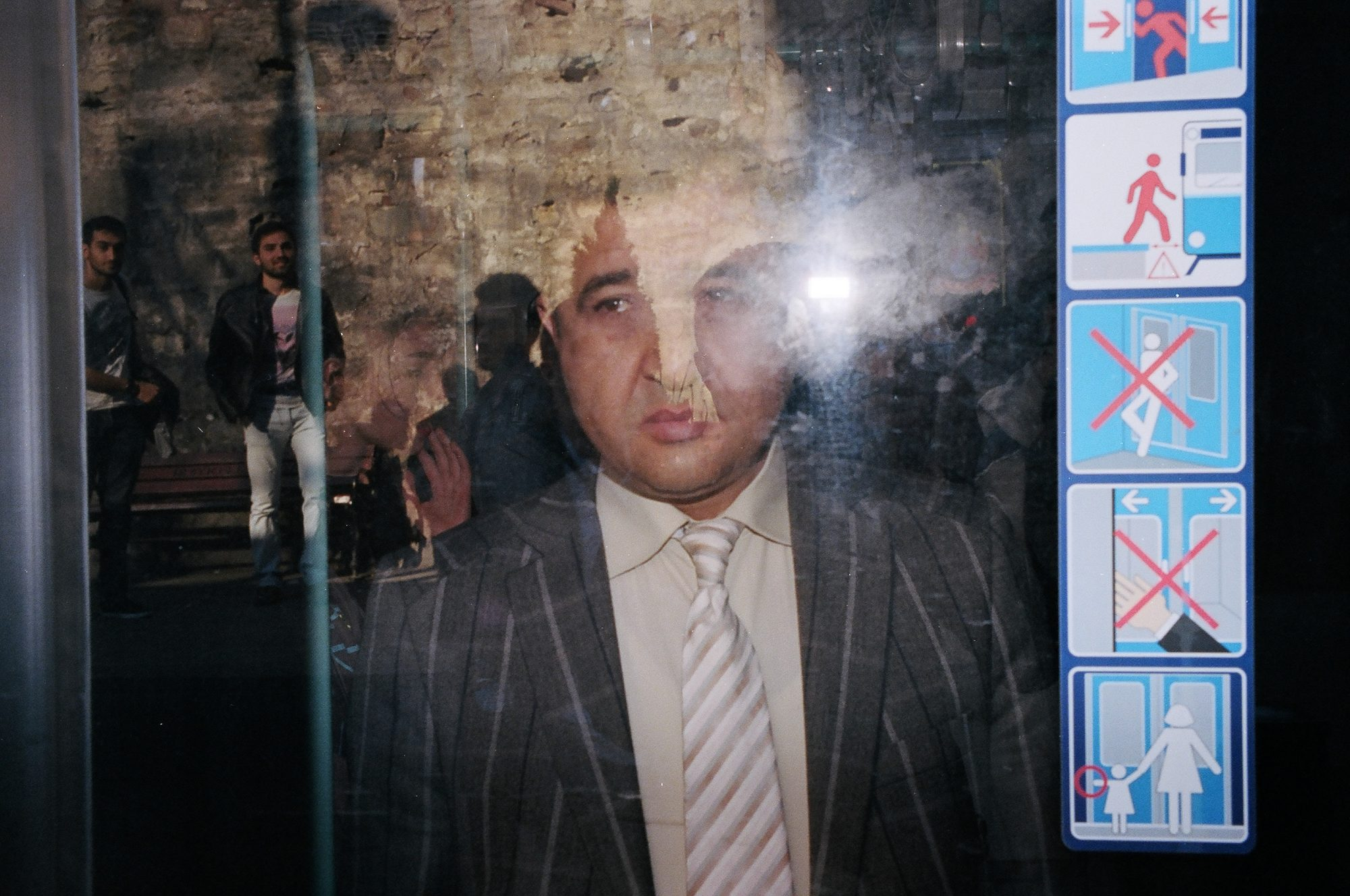 Istanbul man in suit, with flash through glass.