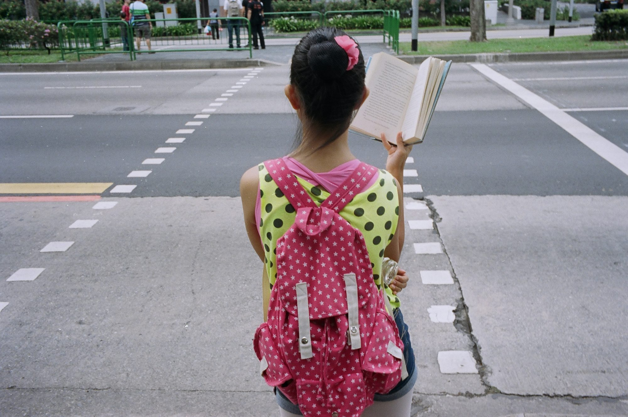 Girl in pink with book. Singapore, 2013