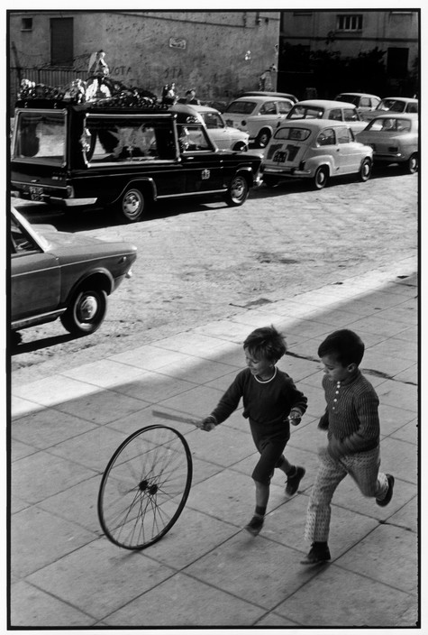 ITALY. Sicily. Palermo. 1971. Henri Cartier Bresson children playing with wheel. And funeral car in top of frame.