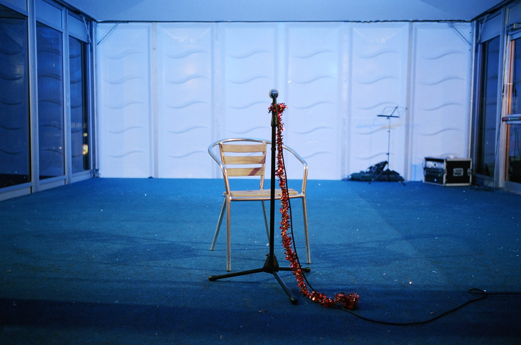 Beauty of a lone chair against a blue background, and microphone stand in red ribbon.