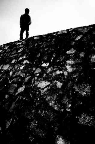 Simple figure to ground composition. Man in silhouette in black in top left of frame against white sky.