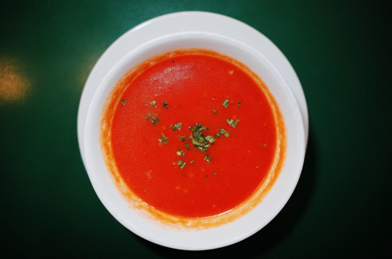 Red tomato soup against green background. Prague, 2017