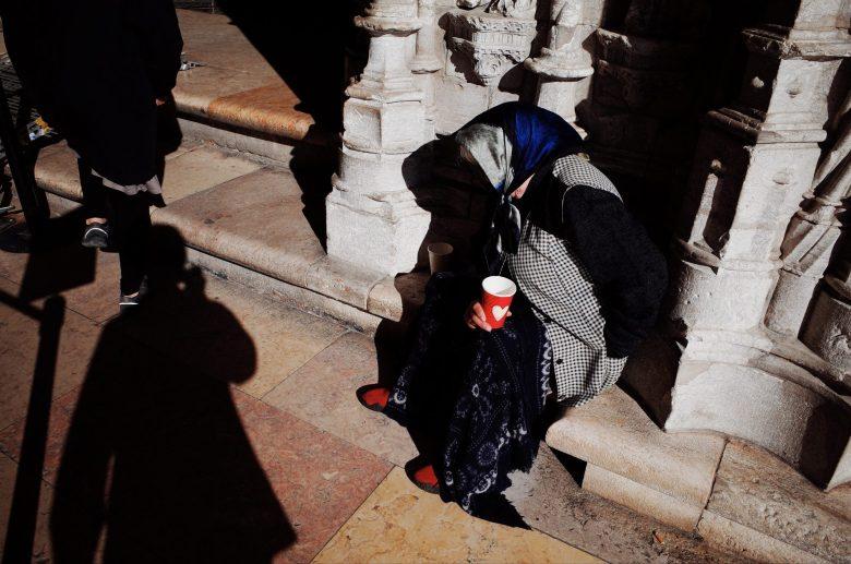 Woman begging outside of Lisbon church