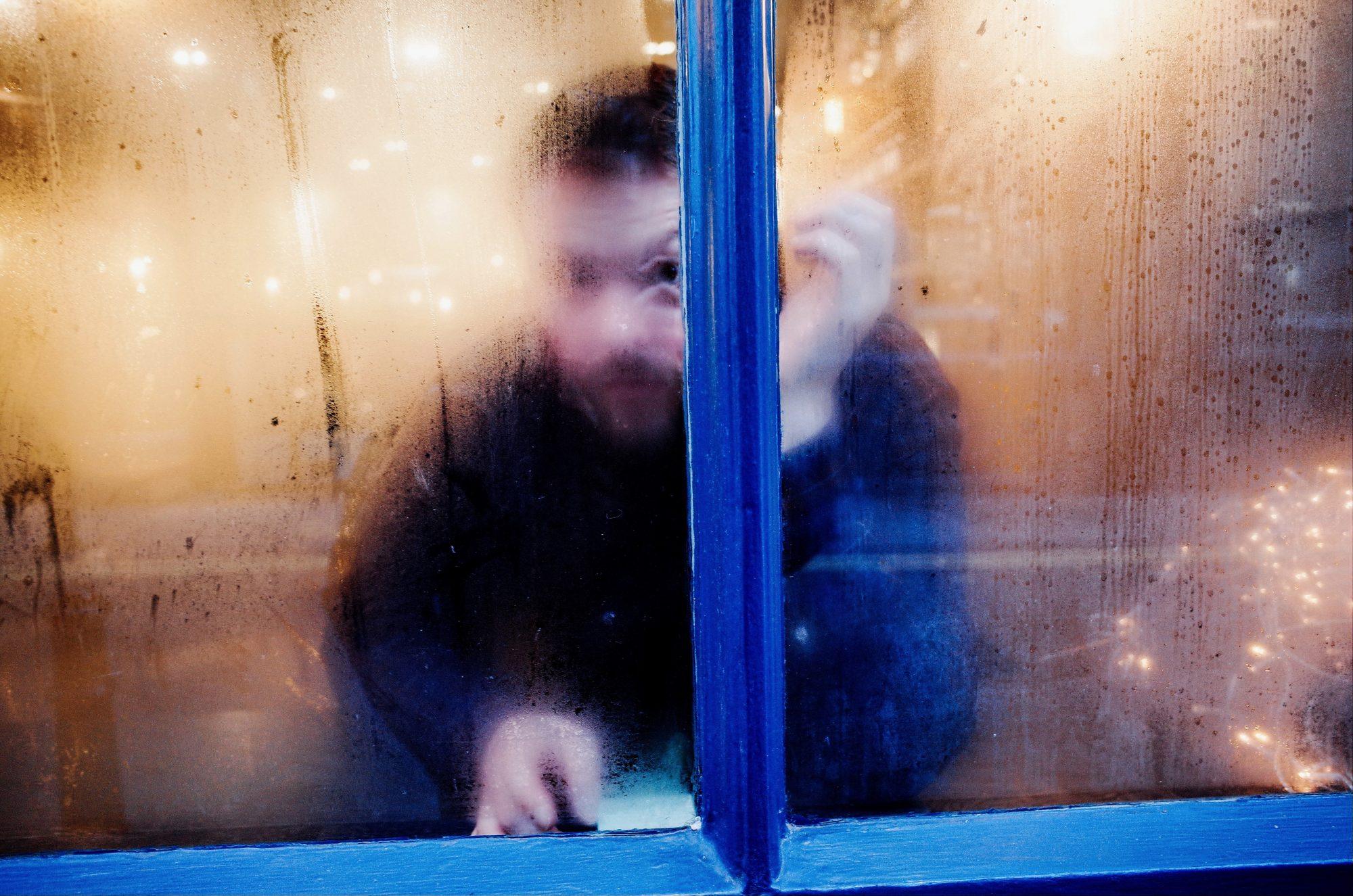 Man with eye looking through foggy window. London, 2018