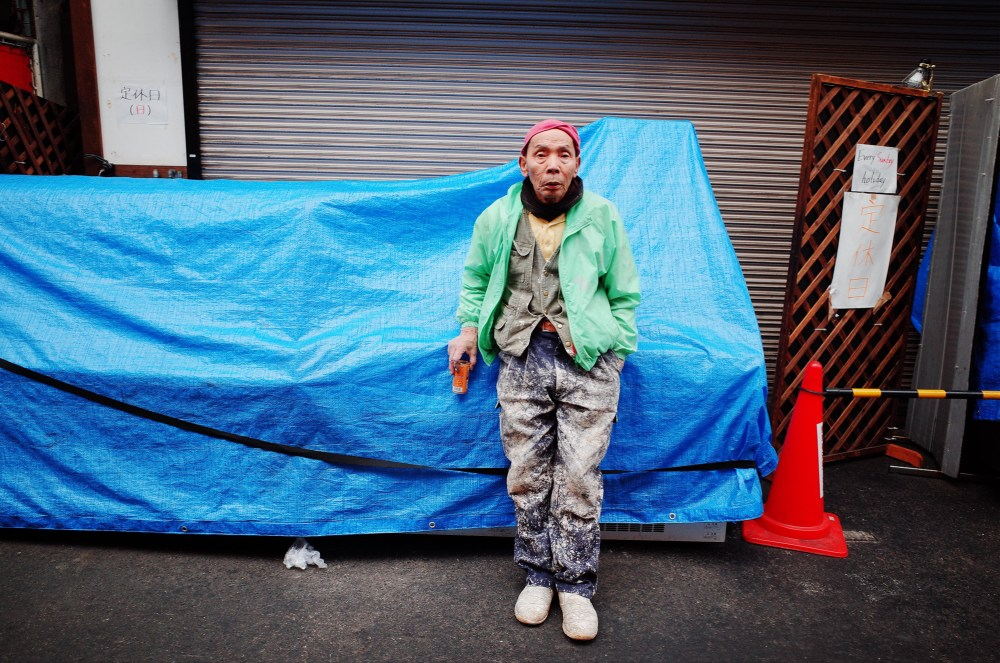 Man in green jacket, blue and orange background. Osaka, 2018