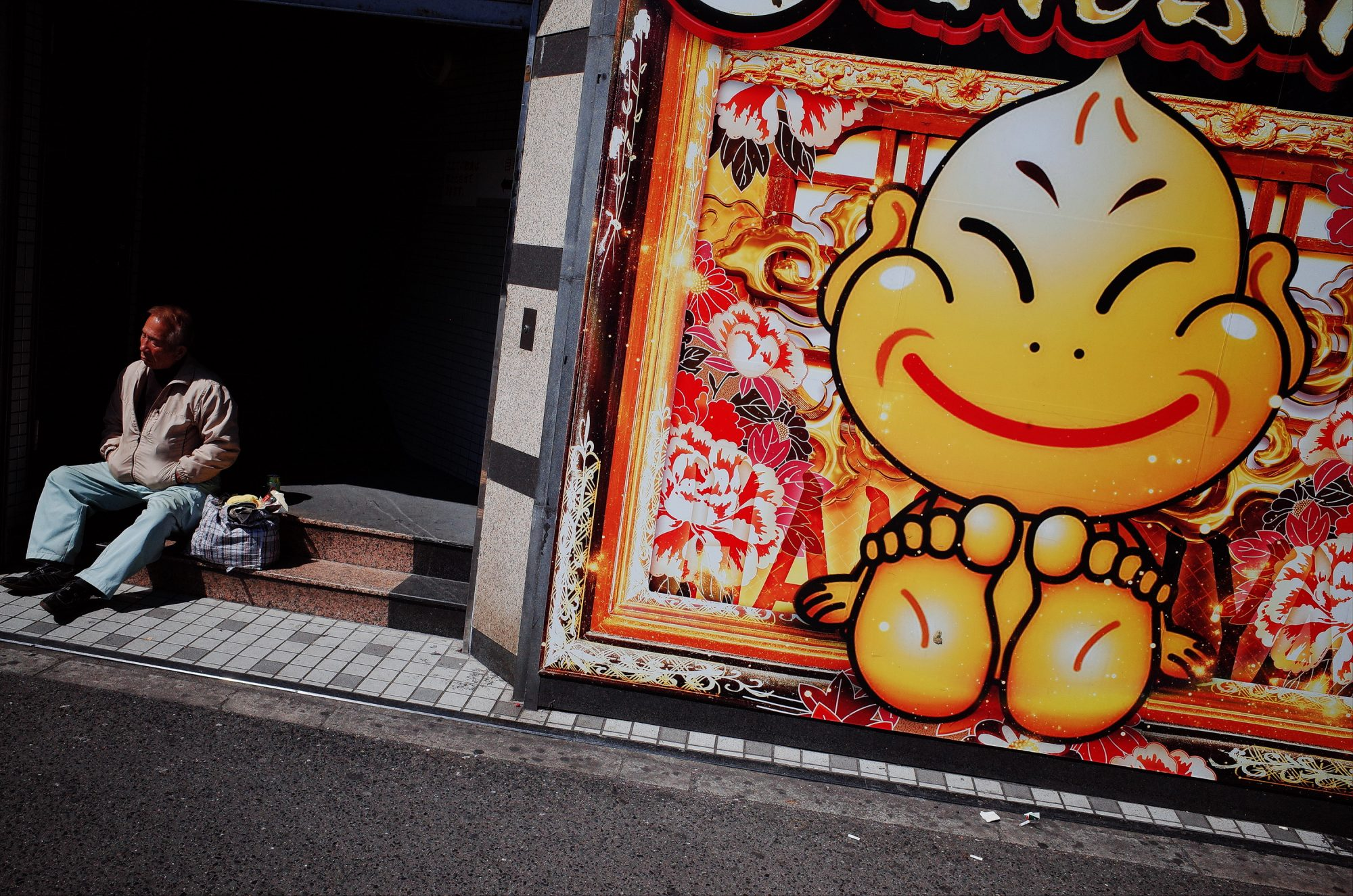 Street scene with man in front of Pachinko. Osaka, 2018