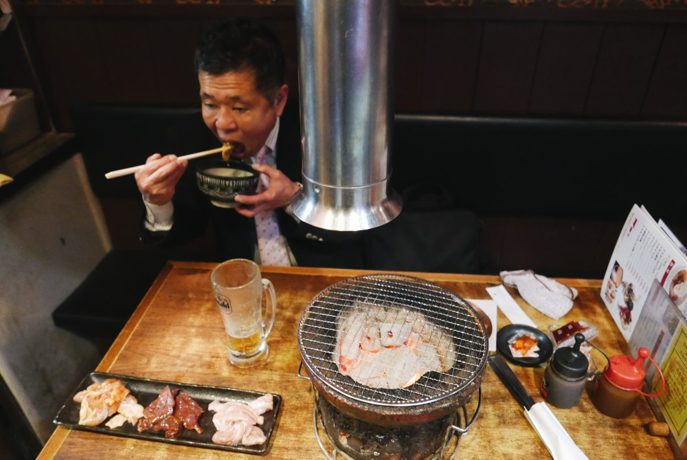 Salary man suit eating offal barbecue. Osaka, 2018