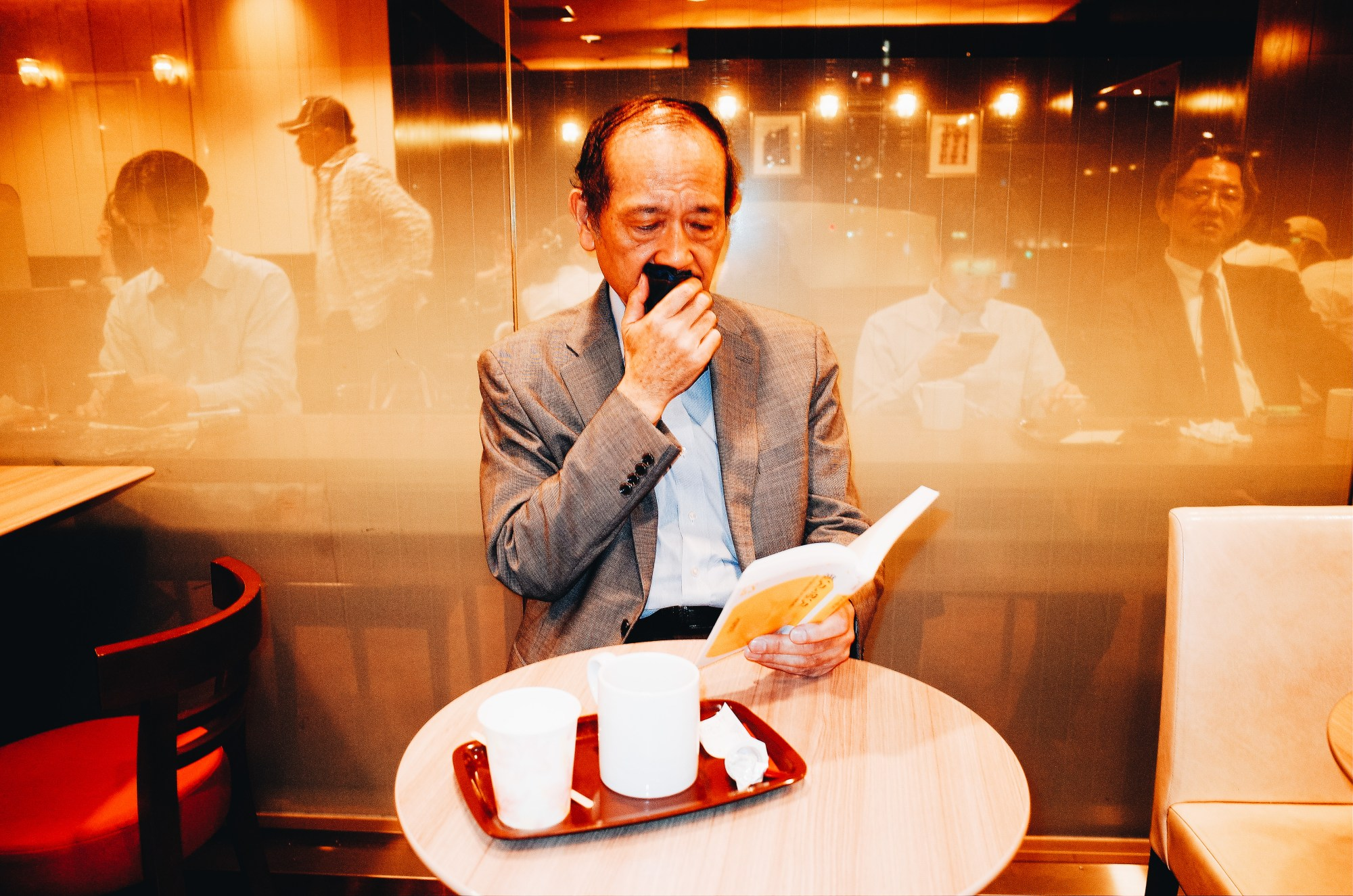 Man covering his mouth with a cloth and reading a book inside Cafe Veloce Coffee shop in Tokyo, 2018