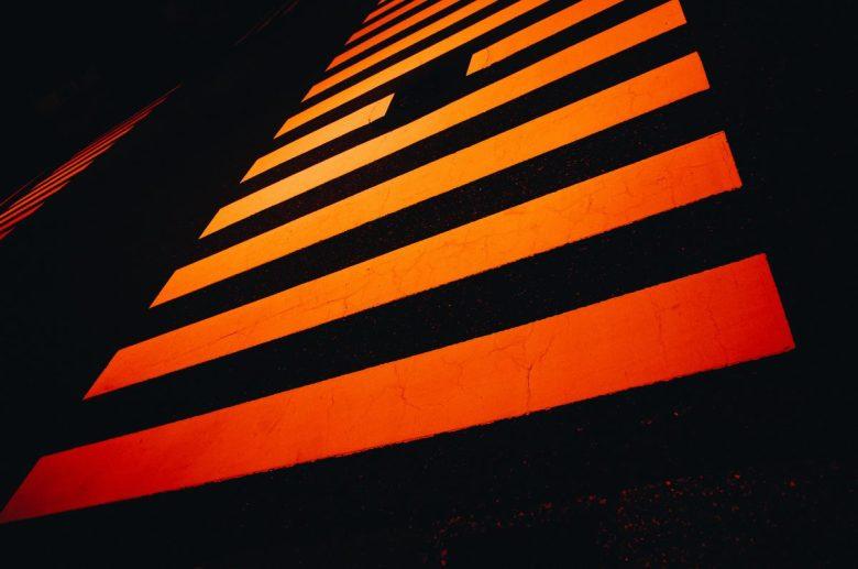 Orange and black lines crosswalk at night. Tokyo, 2018