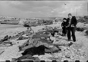FRANCE. Normandy. June, 1944. French fishermen looking at the corpses of slain US soldiers on Omaha Beach.