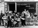 FRANCE. Brittany. Pleybon. 1935. A crowd gathered in front of Mr Pierre Cloarec's bicycle shop. The owner of the shop is racing in the Tour de France.