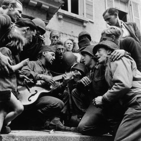 FRANCE. Cherbourg. June 28, 1944. American soldiers and French civilians celebrating the liberation of the city in front of Cherbourg's city hall.