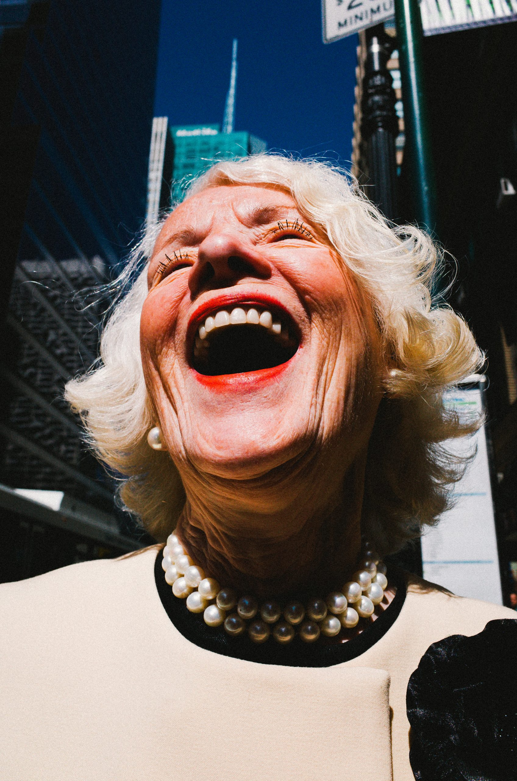ERIC KIM laughing lady white hair red lips blue sky New York City street portrait Ricoh gr ii macro mode 28mm