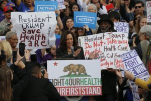 Sen. Kamala Harris, D-Calif., at podium, cheers health care workers to save the Affordable Care Act across the country outside LAC+USC Medical Center in Los Angeles, Sunday, Jan. 15, 2017