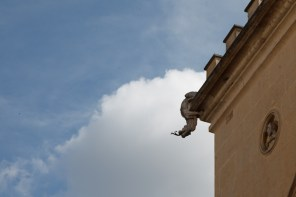 Reggio Emilia, Italy, May 2014: A gargoyle acting as a rain spout dangles off of a building.