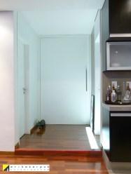 Para dividir a área social da intima utilizamos uma grande porta pivotante. O piso precisou ser elevado para restaurar as tubulações anteriormente destruídas, e com isso embutimos a iluminação. Projeto Erika karpuk