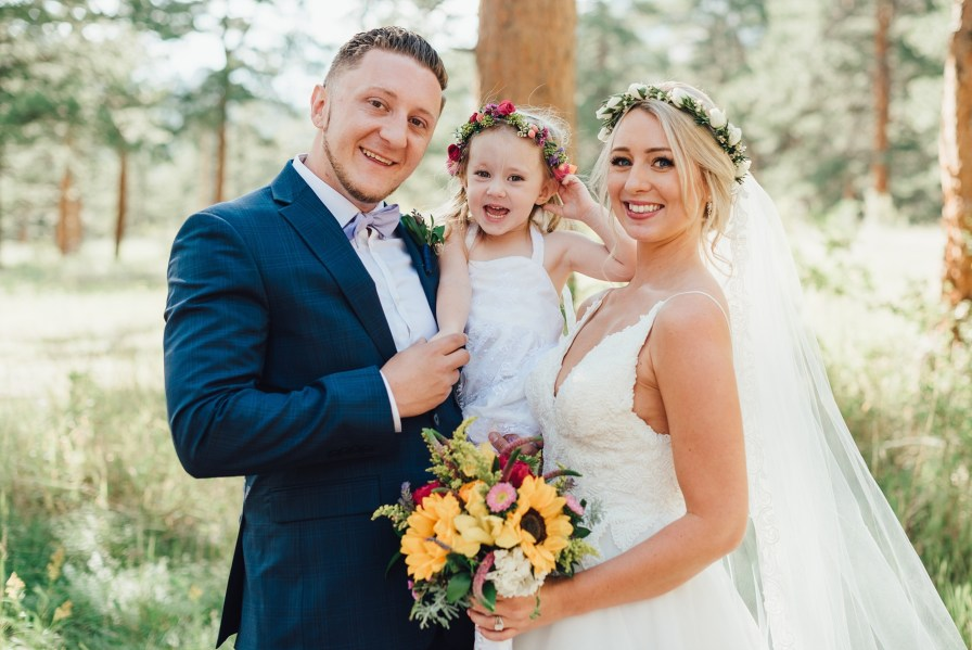 bride and groom with flower girl