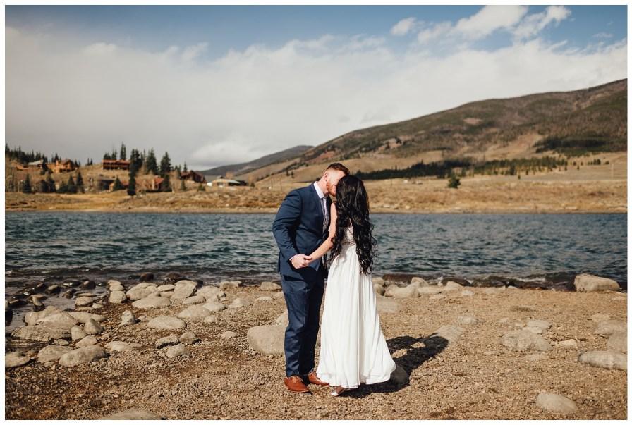 Bride and groom kiss beside Dillon Reservoir