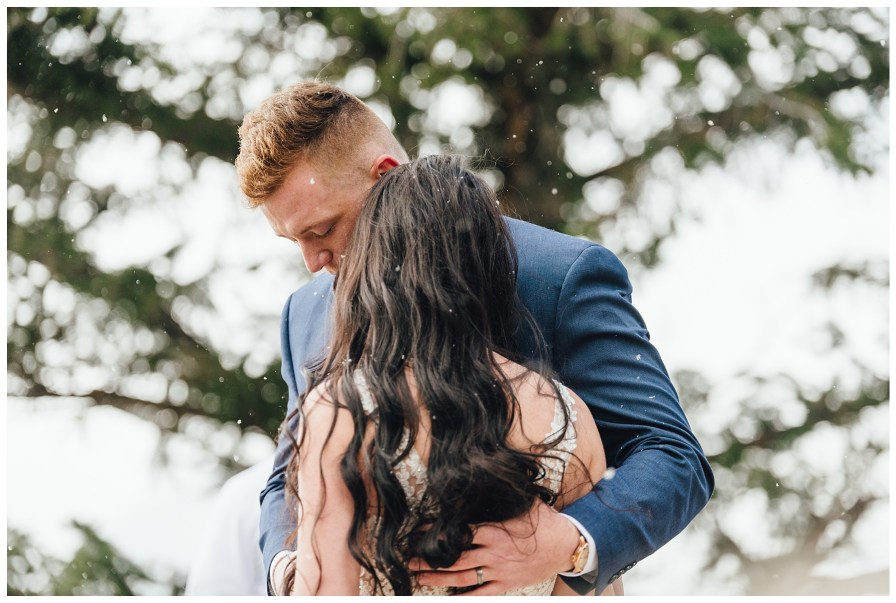 Groom holds his bride while they pray