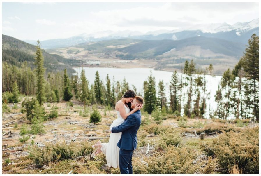 Groom picks up his bride and embraces her atop the mountain