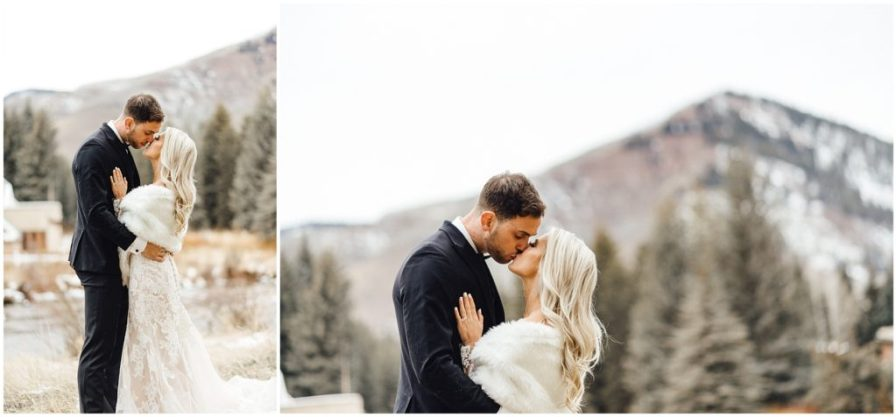 Bride and groom sharing kisses on a mountain in Vail Colorado at their snowy winter elopement