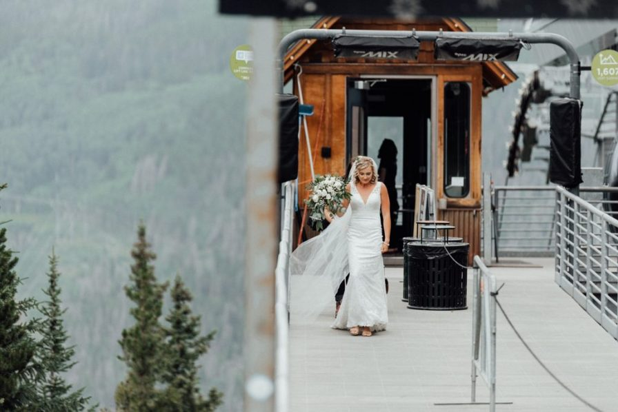 Bride walking off ski lift to meet her groom