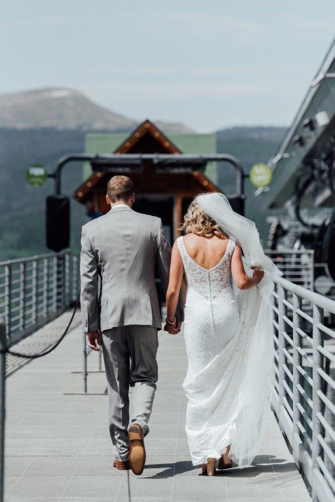 Bride and groom walking along ski lift
